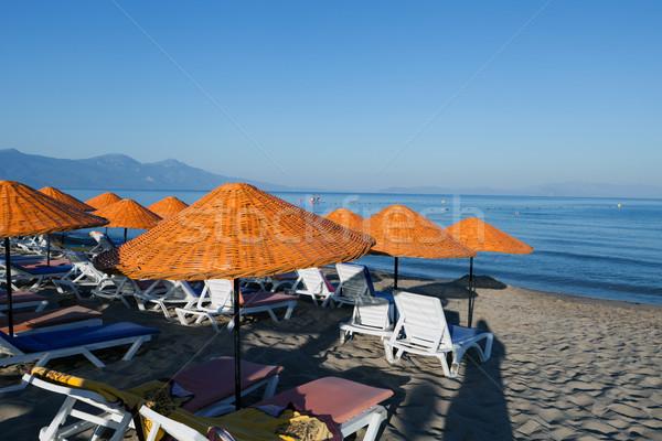Beach loungers and umbrellas on the sea. Stock photo © wjarek