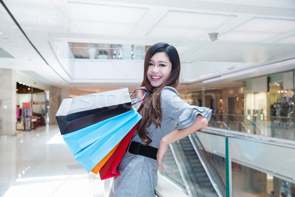Fiatal nő pláza hordoz bevásárlótáskák mosolyog bevásárlóközpont Stock fotó © wxin
