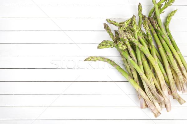 Fresh green asparagus on white wooden background. Top view Stock photo © xamtiw