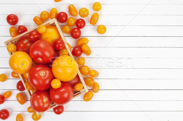 Colorful tomatoes in box on white background, top view. Stock photo © xamtiw