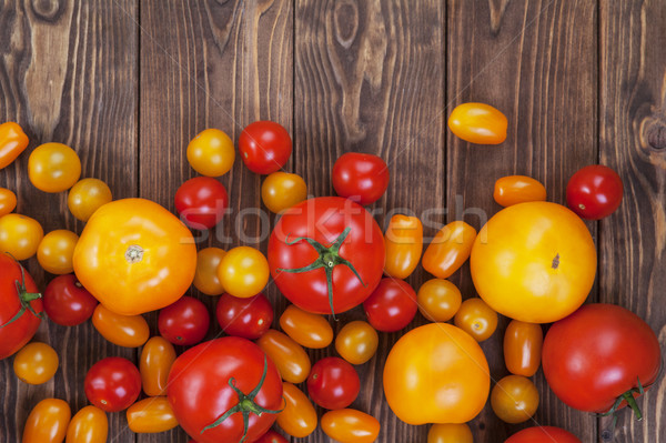 Colorful tomato harvest on wooden table background, top view Stock photo © xamtiw