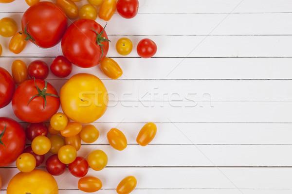 Colorful tomato harvest on white wooden table background, top view Stock photo © xamtiw