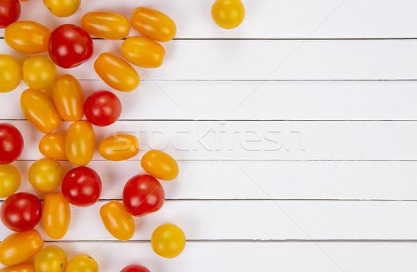 Colorful cherry tomatoes on white table background, top view. Stock photo © xamtiw