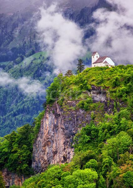 Church on a rock in swiss Alps mountains Stock photo © Xantana