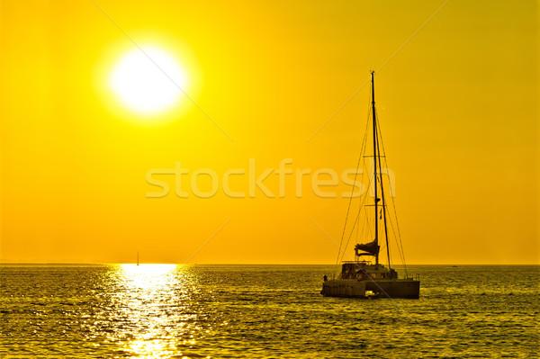 Catamarán velero dorado puesta de sol abierto mar Foto stock © xbrchx