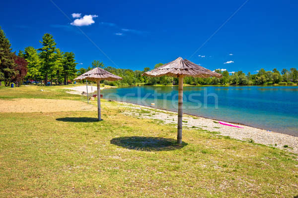 Beach and parasols on Soderica lake Stock photo © xbrchx