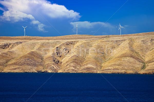 Stone desert island of Pag wind power plants view Stock photo © xbrchx