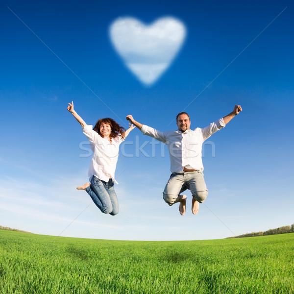 Gelukkig paar springen groene veld blauwe hemel Stockfoto © Yaruta