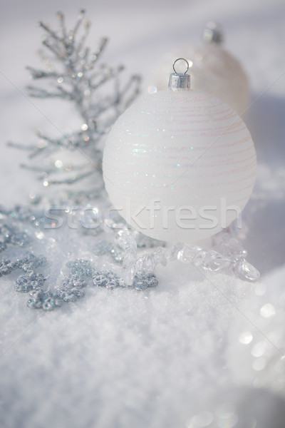 Stock photo: Silver Christmas tree decorations on real snow outdoors. Winter holidays concept. Shallow depth of f