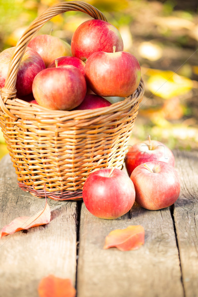 Basket with red apples on wooden table Stock photo © Yaruta
