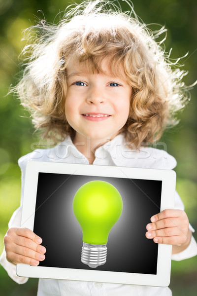 Child holding tablet PC with lightbulb Stock photo © Yaruta