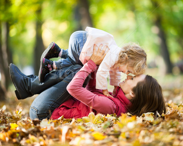 Woman with child having fun in autumn park Stock photo © Yaruta