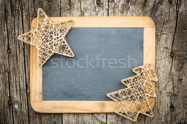 Gold Christmas tree decorations on vintage wooden blackboard Stock photo © Yaruta