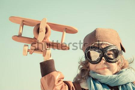 Stock photo: Happy kid playing with toy airplane