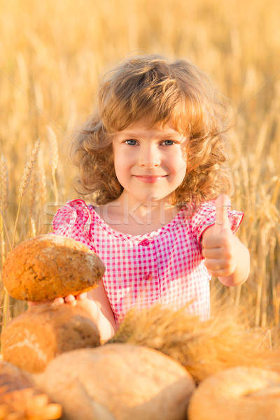 Stock photo: Happy child holding bread