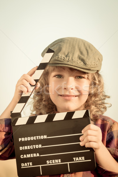 Stock photo: Kid holding clapper board in hands
