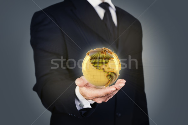 Businessman holding a golden globe Stock photo © ymgerman