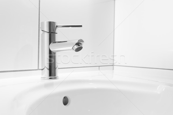 Faucet and white basin in a bathroom Stock photo © ymgerman