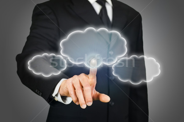 Businessman clicking on thought bubbles Stock photo © ymgerman