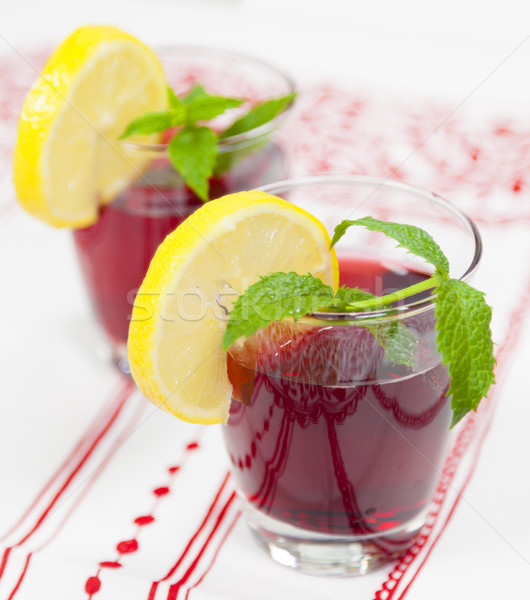 Two glasses of red fruit juice with lemon Stock photo © ymgerman