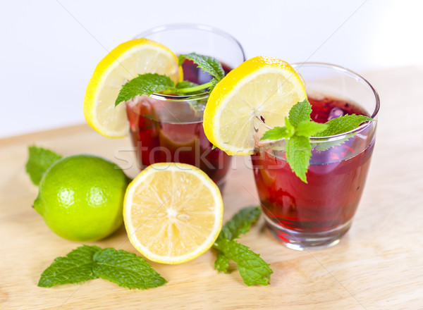 Two glasses of red fruit juice with lemon and lime Stock photo © ymgerman
