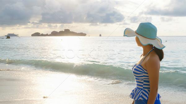 Genç kız plaj gündoğumu şapka mayo Stok fotoğraf © Yongkiet