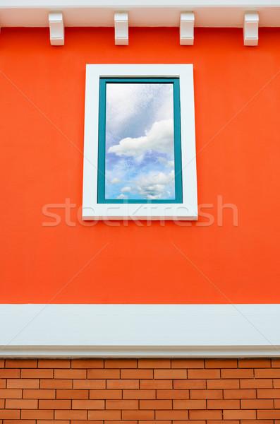 Sky reflection in window glass on orange wall Stock photo © Yongkiet
