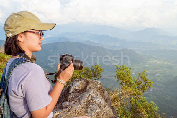 Hiker teen girl holding a camera for photography Stock photo © Yongkiet