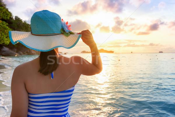 Kız plaj gündoğumu mavi beyaz çizgili Stok fotoğraf © Yongkiet