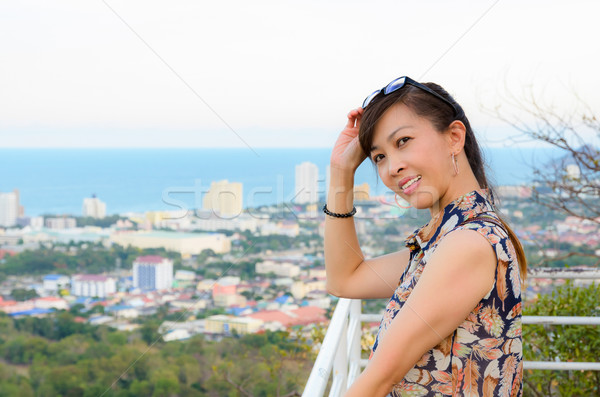 Woman poses on a high point overlooking the city. Stock photo © Yongkiet