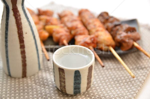 Japanese SAKE cup with char-broiled chicken yakitori Stock photo © YUGOKYOGO