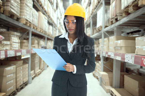 indian woman doing stock tick on warehouse  Stock photo © yuliang11