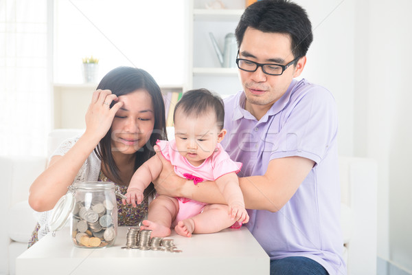 Asian baby putting coins into the glass bottle with help of pare Stock photo © yuliang11