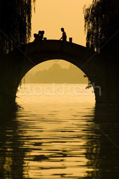 Silhouet mensen lopen brug zonsondergang landschap Stockfoto © yuliang11