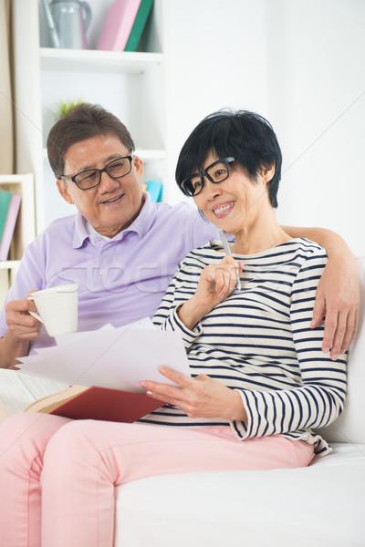 senior asian couple reading a book together at home. Stock photo © yuliang11