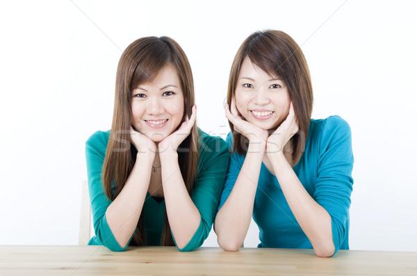 Asya yetişkin gülen iki oturma tablo Stok fotoğraf © yuliang11