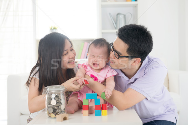 crying asian baby being comforted by chinese parents Stock photo © yuliang11