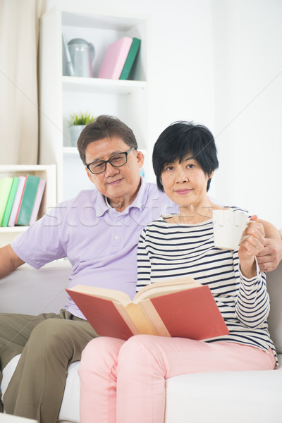 senior asian couple reading a book together at home. Stock photo © yuliang11