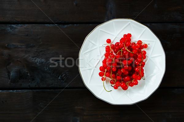 Friss piros ribiszke érett tányér sötét Stock fotó © YuliyaGontar
