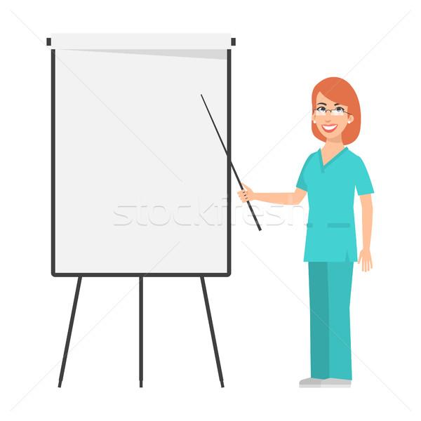 Redhead nurse points to flip chart Stock photo © yuriytsirkunov
