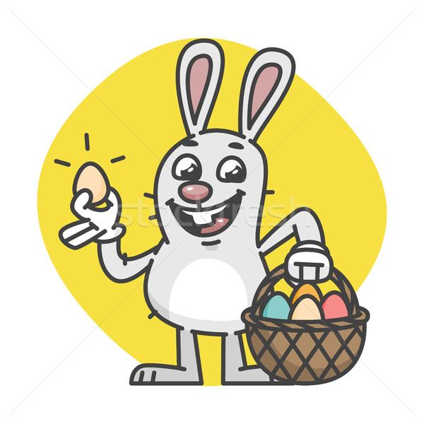 Easter Bunny Holds Egg and Basket With Eggs Stock photo © yuriytsirkunov