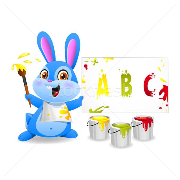 Cheerful rabbit draws on paper Stock photo © yuriytsirkunov