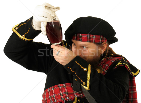 Stock photo: Scottish warrior with the bottle of red wine