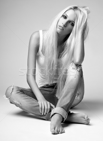 Blonde woman in ragged jeans and vest Stock photo © zastavkin