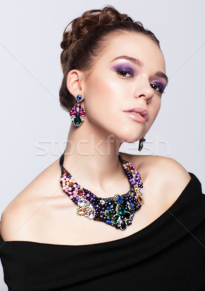 Brown-haired young woman with bijouterie on gray background Stock photo © zastavkin