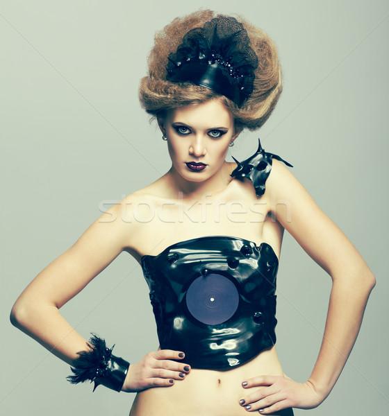 Woman in dress of molten vinyl disk Stock photo © zastavkin