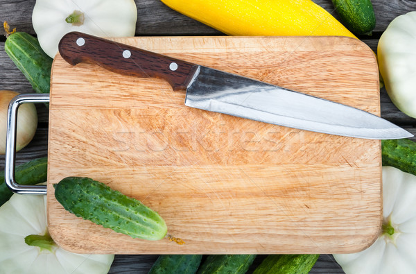 Cutting board, knife, fresh vegetables on wooden table.  Top vie Stock photo © zeffss