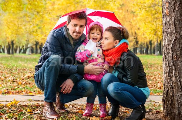 Happy young family under an umbrella in an autumn park Stock photo © zeffss
