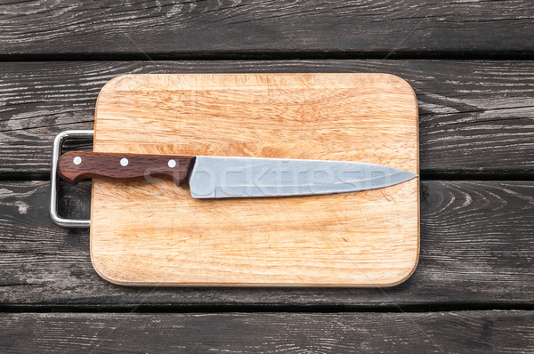Steel knife on a cutting board  wooden background with Stock photo © zeffss