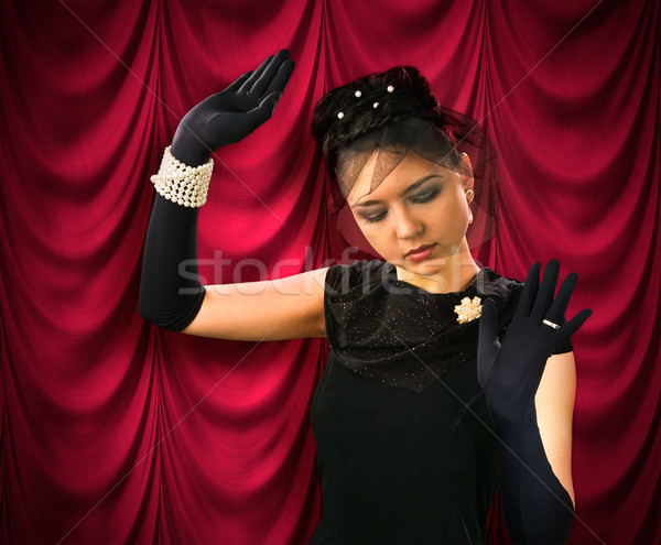 Theatrical actress on the background of red drapes Stock photo © zeffss